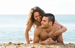 微笑的人和他的女朋友沙子的靠岸 库存照片