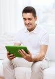微笑的人在家与片剂个人计算机一起使用 免版税库存照片