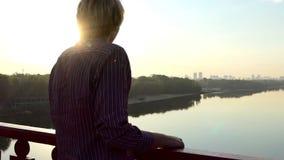 微笑的人在slo mo享受dnipro河的一个美丽如画的看法从桥梁的 股票录像