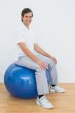 微笑的人坐在医院健身房的锻炼球 免版税库存图片