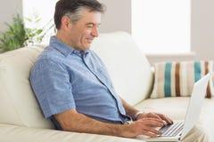 微笑的人坐沙发使用膝上型计算机 库存图片