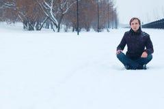 年轻微笑的人坐雪道靠近公园在冬天 库存照片