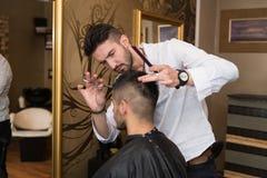 微笑的人客户的男性美发师切口头发 免版税图库摄影