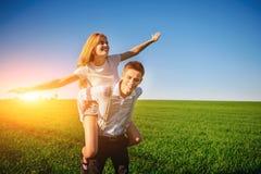 微笑的人拿着他的后面愉快的妇女,拔出她的胳膊并且模仿飞行以蓝色s为背景 免版税库存照片