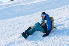微笑的人挡雪板休息坐 免版税库存图片