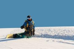 微笑的人挡雪板休息的下跪和显示赞许 库存图片