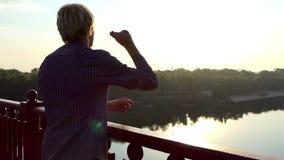 微笑的人攫取他的在一座桥梁的手指在Dnipro在日落在Slo Mo 影视素材