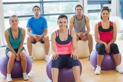 微笑的人民坐在明亮的健身房的锻炼球 免版税库存照片