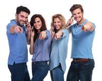 微笑的人民谈话在电话和指向手指 免版税库存图片