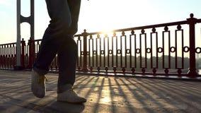 微笑的人沿在精采日落射线的一座现代桥梁去在Slo Mo 影视素材