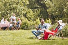 微笑的人用啤酒谈话与朋友,当放松在sunbeds在庭院里时 实际照片 免版税图库摄影