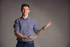 微笑的人画象蓝色衬衣的在灰色演播室背景摆在照相机的,姿势:看此 免版税库存图片