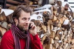 微笑的人谈话在一个手机室外在冬天期间 免版税库存图片