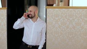 微笑的人谈话在倾斜对墙壁的电话 影视素材