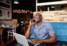 微笑的人谈话在手机,当坐在与膝上型计算机时的咖啡馆 免版税库存照片