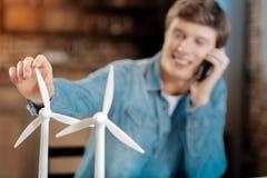 微笑的人谈话在电话和感人的风轮机 免版税库存图片