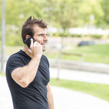 微笑的人谈话用电话。 免版税库存照片