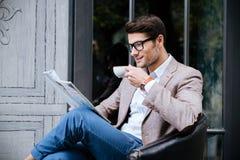 微笑的人饮用的咖啡和读在室外咖啡馆的杂志 免版税图库摄影