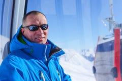 微笑的人,在滑雪电缆车客舱的佩带的太阳镜 免版税库存照片