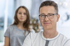 微笑的人画象有在家站立在背景中的女儿的 库存图片