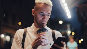 微笑的人usingn智能手机在夜城市 使用智能手机的英俊的年轻人在晚上和喝冰冻咖啡 股票录像