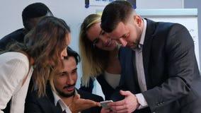 微笑的企业队与智能手机,观看的somethng一起使用有趣在办公室 股票录像