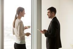 微笑的企业队员谈话在办公室在咖啡增殖比期间 库存照片
