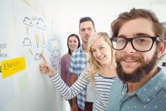 微笑的企业队画象,当支持有稠粘的笔记和图画的时墙壁 免版税库存照片