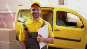 微笑的传讯者画象与剪贴板身分的在黄色搬运车附近 股票视频