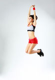 年轻微笑的体育妇女跳跃 图库摄影
