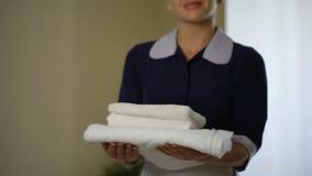 微笑的佣人转动与干净的雪白毛巾的,酒店房间预定 股票视频
