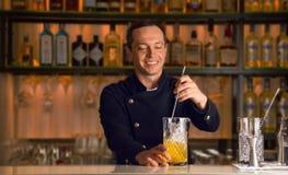 微笑的侍酒者引起混合的杯子的内容 免版税库存图片