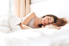 微笑的俏丽的夫人在床上在户内 闭合的眼睛 免版税库存图片