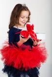 微笑的俏丽的女孩拿着有红色的礼物盒 库存图片