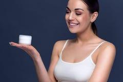 微笑的俏丽的妇女对负奶油色为她的皮肤 免版税库存图片