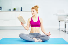 微笑的信奉瑜伽者妇女阅读书 免版税库存照片