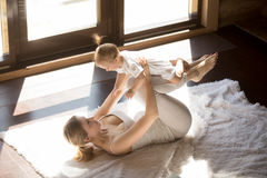 年轻微笑的信奉瑜伽者母亲和在家行使小的女儿 免版税库存照片