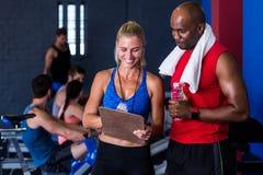 微笑的健身辅导员谈论与人在健身房 免版税库存照片