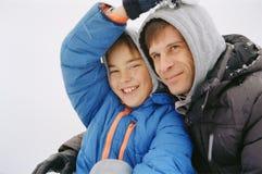 微笑的儿子和爸爸冬天画象  免版税库存照片