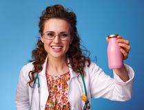 微笑的儿科医生妇女瓶在蓝色的饮用的酸奶 库存图片