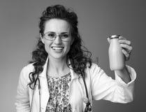 微笑的儿科医生妇女瓶饮用的酸奶  免版税库存照片