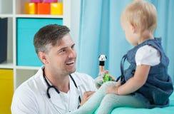 微笑的儿科医生和他的小患者 库存照片