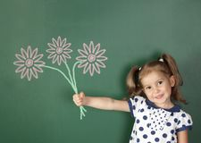 微笑的儿童女孩在学校黑板附近拿着拉长的花 免版税库存照片