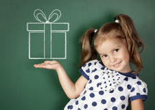 微笑的儿童女孩在学校黑板附近拿着拉长的礼物盒 免版税库存图片