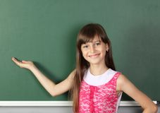 微笑的儿童女孩在空的学校黑板附近握他的手, 免版税库存照片