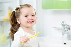 微笑的儿童女孩掠过的牙 免版税库存图片