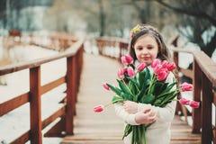 微笑的儿童女孩春天画象有郁金香花束的在步行 免版税库存图片