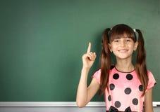 微笑的儿童女孩显示与手指空的学校黑板, c 库存照片