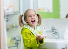 微笑的儿童小女孩洗涤的手在卫生间里 库存图片