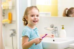 微笑的儿童掠过的牙在卫生间里 免版税库存照片